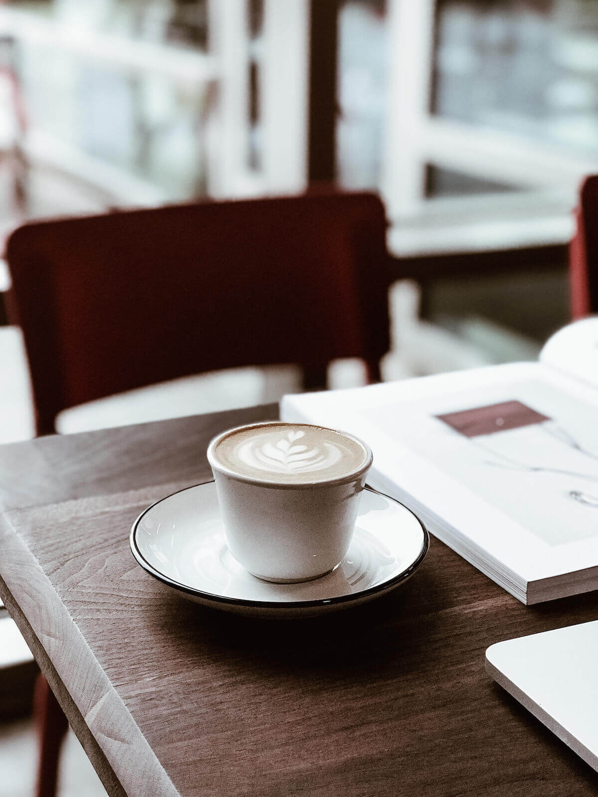 vanilla latte and book on table with chair