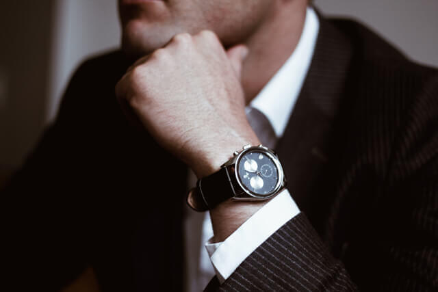 Man sitting down thinking with watch on wrist